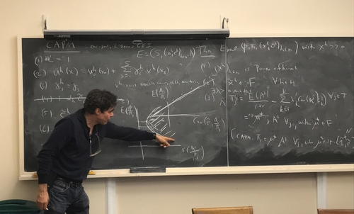 Geanakoplos pointing to an equation on the blackboard